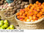 Купить «appetizing apricots in wicker baskets on counter in market», фото № 29959248, снято 26 мая 2018 г. (c) Татьяна Яцевич / Фотобанк Лори