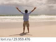 Купить «Man standing with arms outstretched on the beach », фото № 29959476, снято 6 ноября 2018 г. (c) Wavebreak Media / Фотобанк Лори