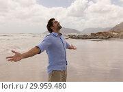 Купить «Man standing with arms outstretched on the beach », фото № 29959480, снято 6 ноября 2018 г. (c) Wavebreak Media / Фотобанк Лори