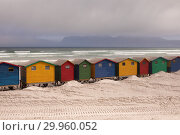 Купить «Multicoloured beach huts on beach with ocean in the background», фото № 29960052, снято 14 ноября 2018 г. (c) Wavebreak Media / Фотобанк Лори