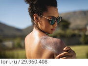 Купить «Young mixed-race woman rubbing sunscreen on shoulders», фото № 29960408, снято 7 ноября 2018 г. (c) Wavebreak Media / Фотобанк Лори
