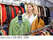 Купить «Positive girl looking for new leather jacket during shopping in retail shop», фото № 29961184, снято 5 сентября 2018 г. (c) Яков Филимонов / Фотобанк Лори