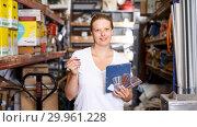 Купить «Woman standing near shelves holding notebook and samples in build store», фото № 29961228, снято 20 сентября 2018 г. (c) Яков Филимонов / Фотобанк Лори