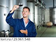 Купить «Man in uniform looking at wine», фото № 29961548, снято 17 июня 2019 г. (c) Яков Филимонов / Фотобанк Лори