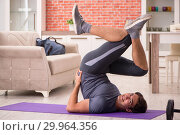 Young handsome man doing sport exercises at home. Стоковое фото, фотограф Elnur / Фотобанк Лори
