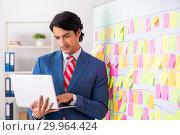 Купить «Young handsome employee with many conflicting priorities», фото № 29964424, снято 16 октября 2018 г. (c) Elnur / Фотобанк Лори