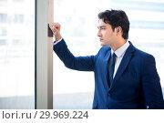 Купить «Young handsome businessman standing at the window», фото № 29969224, снято 2 августа 2018 г. (c) Elnur / Фотобанк Лори