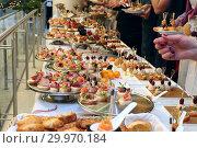Купить «Банкетный стол с холодными закусками. Люди у праздничного фуршетного стола», фото № 29970184, снято 26 декабря 2018 г. (c) Татьяна Белова / Фотобанк Лори