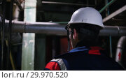 Купить «A man engineer in a helmet walking in manufacturing plant and looking around», видеоролик № 29970520, снято 16 февраля 2019 г. (c) Константин Шишкин / Фотобанк Лори