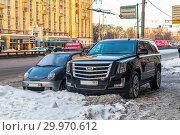 Купить «Два автомобиля, компактный Daewoo и большой внедорожник Cadillac, стоят рядом на зимней московской улице», фото № 29970612, снято 13 февраля 2018 г. (c) Владимир Сергеев / Фотобанк Лори