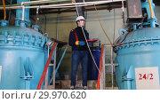 Купить «A man engineer walks to a equipment and making notes about manufacturing plant», видеоролик № 29970620, снято 16 февраля 2019 г. (c) Константин Шишкин / Фотобанк Лори