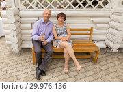 Купить «Beautiful elegant middle-aged couple posing sitting on a bench smiling at a holiday.», фото № 29976136, снято 18 мая 2018 г. (c) Акиньшин Владимир / Фотобанк Лори