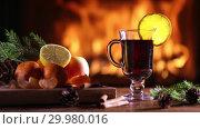 Купить «A glass of mulled wine (gluhwein) and a plate of fruit on the background of a burning fireplace», видеоролик № 29980016, снято 17 февраля 2019 г. (c) Алексей Кузнецов / Фотобанк Лори