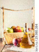 Купить «Processing of an agricultural crop of red and green apples. Homemade preparations, healthy diet vegetarian food. Spiced apple cider vinegar, juice, cider in a glass jug next to a box of ripe fruit», фото № 29980384, снято 16 февраля 2019 г. (c) Светлана Евграфова / Фотобанк Лори