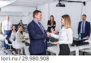Купить «businessman and businesswoman shaking hands in office», фото № 29980908, снято 21 апреля 2018 г. (c) Яков Филимонов / Фотобанк Лори
