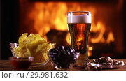 Купить «Still life of a glass of lager beer and chips, olives and nuts on the background of a burning fireplace», видеоролик № 29981632, снято 18 февраля 2019 г. (c) Алексей Кузнецов / Фотобанк Лори