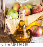 Купить «Processing of an agricultural crop of red and green apples. Home canning, healthy diet vegetarian food. Spiced apple cider vinegar, juice, cider in a glass jug next to a box of ripe fruit», фото № 29996288, снято 16 февраля 2019 г. (c) Светлана Евграфова / Фотобанк Лори