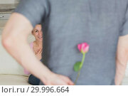 Husband hiding flower behind back. Стоковое фото, агентство Wavebreak Media / Фотобанк Лори