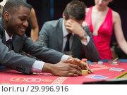 Купить «Man winning jackpot as other man is being comforted by woman», фото № 29996916, снято 20 июля 2012 г. (c) Wavebreak Media / Фотобанк Лори