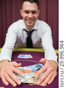 Купить «Man grabbing money at poker table», фото № 29996964, снято 20 июля 2012 г. (c) Wavebreak Media / Фотобанк Лори