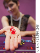 Купить «Woman sitting at table while holding dices», фото № 29997248, снято 20 июля 2012 г. (c) Wavebreak Media / Фотобанк Лори