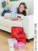 Купить «Woman looking at credit card and phoning», фото № 29999148, снято 16 августа 2012 г. (c) Wavebreak Media / Фотобанк Лори