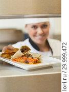 Купить «Cheerful chef giving plate through order station», фото № 29999472, снято 1 августа 2012 г. (c) Wavebreak Media / Фотобанк Лори