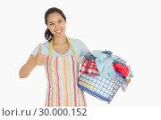 Купить «Woman carrying laundry basket and giving thumbs up», фото № 30000152, снято 8 августа 2012 г. (c) Wavebreak Media / Фотобанк Лори