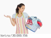 Купить «Quizzical looking young woman looking at basket», фото № 30000156, снято 8 августа 2012 г. (c) Wavebreak Media / Фотобанк Лори