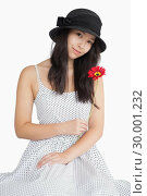 Купить «Woman holding flower in a polka dot dress», фото № 30001232, снято 23 августа 2012 г. (c) Wavebreak Media / Фотобанк Лори