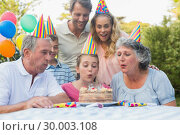 Cheerful extended family watching girl blowing out birthday candles. Стоковое фото, агентство Wavebreak Media / Фотобанк Лори