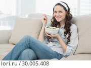 Купить «Pretty casual woman on cosy couch eating salad», фото № 30005408, снято 21 мая 2013 г. (c) Wavebreak Media / Фотобанк Лори