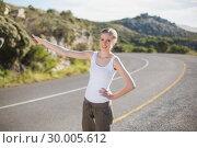 Stranded woman hitching a lift and smiling at camera. Стоковое фото, агентство Wavebreak Media / Фотобанк Лори