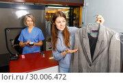 Купить «Portrait of cheerful female laundry customer holding clean clothes on hanger», фото № 30006472, снято 22 января 2019 г. (c) Яков Филимонов / Фотобанк Лори