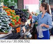 Купить «Female is looking on shelves with zucchini in the market.», фото № 30006592, снято 29 апреля 2018 г. (c) Яков Филимонов / Фотобанк Лори