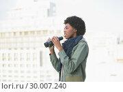 Купить «Curious casual model holding binoculars», фото № 30007240, снято 7 июня 2013 г. (c) Wavebreak Media / Фотобанк Лори