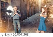 Купить «Photographer shooting female model on city street», фото № 30007368, снято 5 октября 2018 г. (c) Яков Филимонов / Фотобанк Лори