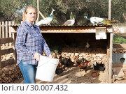 Купить «Woman farmer feeds poultry in the backyard of the farm», фото № 30007432, снято 15 декабря 2018 г. (c) Яков Филимонов / Фотобанк Лори