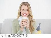 Купить «Cheerful cute blonde holding coffee sitting on cosy sofa», фото № 30007716, снято 12 июня 2013 г. (c) Wavebreak Media / Фотобанк Лори