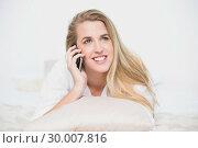 Купить «Smiling model on the phone lying on cosy bed», фото № 30007816, снято 12 июня 2013 г. (c) Wavebreak Media / Фотобанк Лори