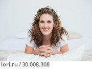 Купить «Portait of smiling woman lying on bed», фото № 30008308, снято 5 июня 2013 г. (c) Wavebreak Media / Фотобанк Лори