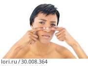 Frowning black haired woman popping a pimple. Стоковое фото, агентство Wavebreak Media / Фотобанк Лори