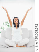 Купить «Cheerful black haired woman in white clothes raising her arms», фото № 30008572, снято 29 мая 2013 г. (c) Wavebreak Media / Фотобанк Лори