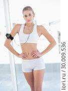 Купить «Serious young blonde model posing with hands on the hips», фото № 30009536, снято 6 июня 2013 г. (c) Wavebreak Media / Фотобанк Лори