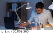 Купить «businessman with papers and laptop at night office», видеоролик № 30009560, снято 11 февраля 2019 г. (c) Syda Productions / Фотобанк Лори