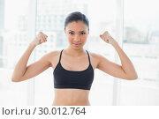 Dynamic dark haired model in sportswear showing her strength. Стоковое фото, агентство Wavebreak Media / Фотобанк Лори