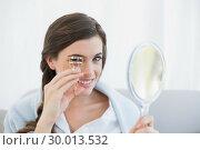 Купить «Smiling casual brown haired woman in white pajamas using an eyelash curler», фото № 30013532, снято 18 июня 2013 г. (c) Wavebreak Media / Фотобанк Лори