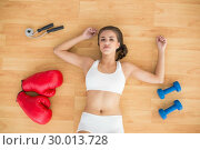 Купить «Sporty brunette lying next to jump rope red boxing gloves and dumbbells», фото № 30013728, снято 19 июня 2013 г. (c) Wavebreak Media / Фотобанк Лори