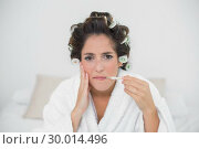 Купить «Grimacing natural brunette holding thermometer», фото № 30014496, снято 21 июня 2013 г. (c) Wavebreak Media / Фотобанк Лори