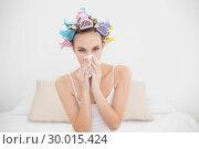 Купить «Cute natural brown haired woman in hair curlers sneezing in a tissue», фото № 30015424, снято 26 июня 2013 г. (c) Wavebreak Media / Фотобанк Лори